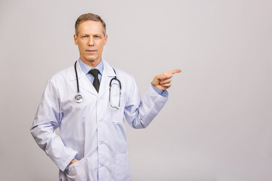 Doctor senior man, medical professional pointing away side with finger isolated over grey background.