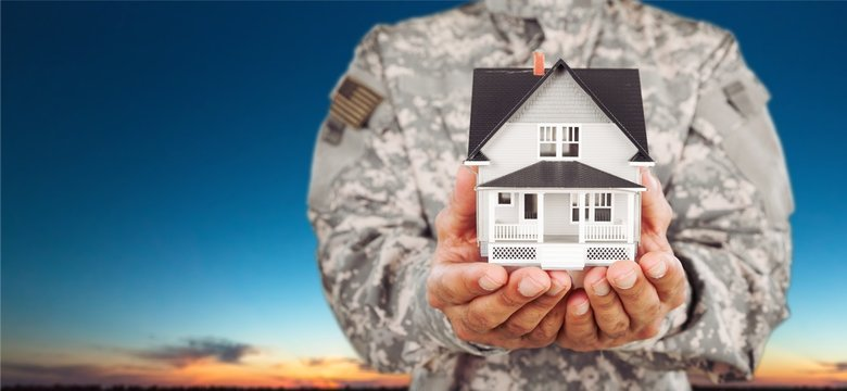 Soldier man holding a model of the house