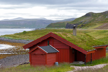 Traditional Norwegian red house on the fjord in cloudy weather
