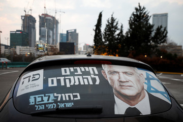 A Blue and White party election campaign poster, depicting party leader Benny Gantz, is seen on a car in Tel Aviv