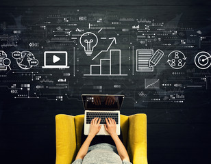 Wall Mural - Content marketing concept with person using a laptop in a chair