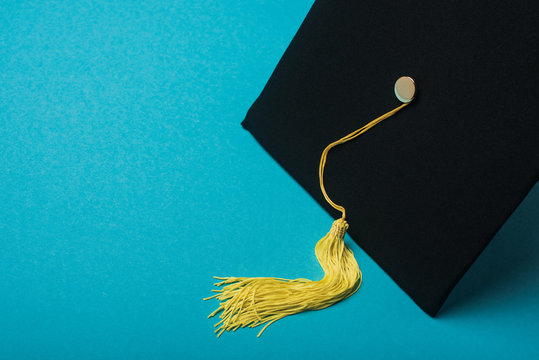 Graduation cap with yellow tassel on blue background