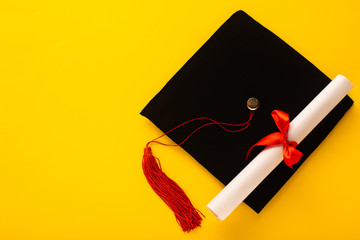 Top view of black graduation cap with red tassel with diploma on top on yellow background