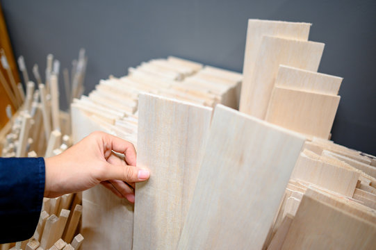 Male hand designer choosing beige balsa wood plank in stationery shop. Wooden material for making art and craft model. Wood industry concept