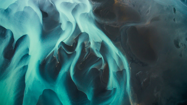 Aerial view from above on a green and blue glacier river stream in  South Iceland. Beautiful patterns, textures and structures. Melting glacier,  Global warming and climate change concept
