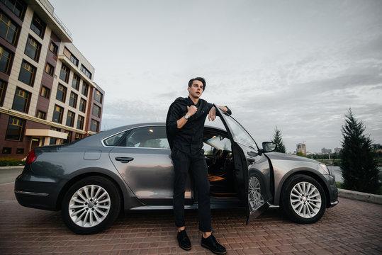 A stylish businessman smokes cigars near a luxury car. Fashion and business