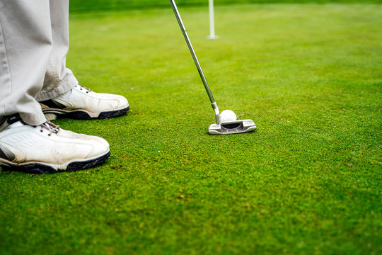 senior person putting on the green on a golf course