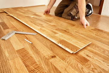 A craftsman lays oak parquet with a click system