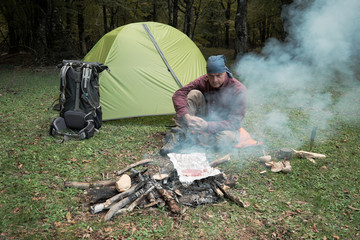 Man Cooking Meat And Mushrooms On Campfire Near Tent And Backpack