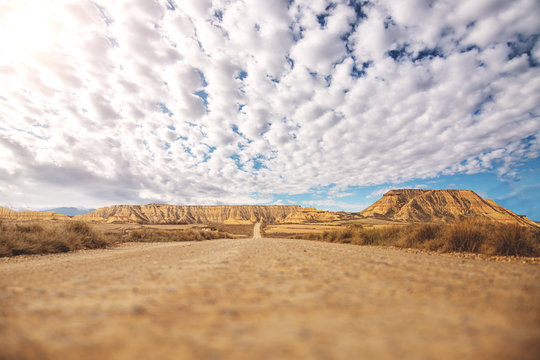 Empty road with brown soil goes into distance among dry shrubs and brown mountains and blue sky with white clouds on background at Bardenas Reales