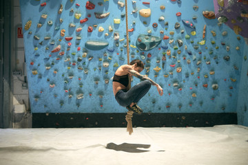 Side view of smiling enthusiastic tattooed woman holding rope and jumping in gym with wall with ledges for climbers