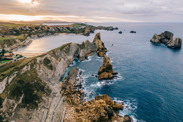 Amazing aerial landscape of steep rocky shore and breathtaking wavy ocean in cloudy day in Pielagos, Cantabria, Santander, Spain