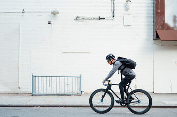 Side view of contemporary male cyclist in black helmet and eyeglasses surfing on mobile phone on white wall background