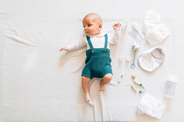 Top view of surprised newborn infant in casual wear lying on bed near toys looking away