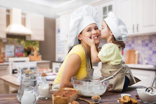 Happy mother and child cooking on kitchen interior