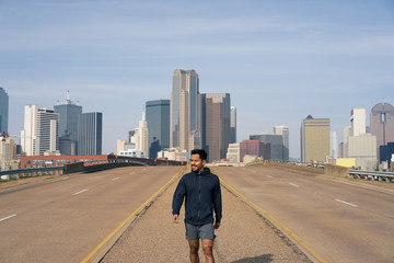 Young Hispanic male athlete in sports clothing looking away after workout standing on side of road in downtown Dallas, Texas