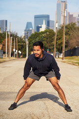 Hispanic male gymnast in active wear standing and reaching out arm to opposite foot in downtown Dallas, USA