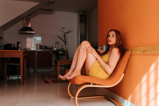 Side view of thoughtful redhead woman looking away while resting on chair at home holding a cup of hot beverage in the morning