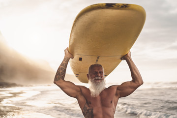Happy fit senior having fun surfing at sunset time - Sporty bearded man training with surfboard on the beach - Elderly healthy people lifestyle and extreme sport concep
