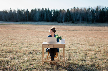travelling woman working on a desk and laptop in a field at sunset