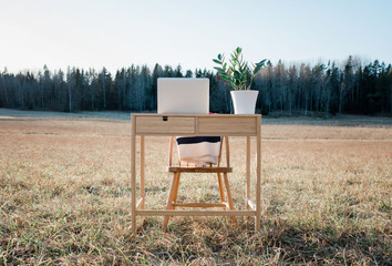 A desk and laptop home office in the middle of a field outdoors