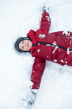 Caucasian boy in red jacket making snow angel