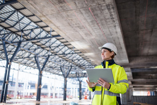 A woman engineer with tablet standing on construction site, working.