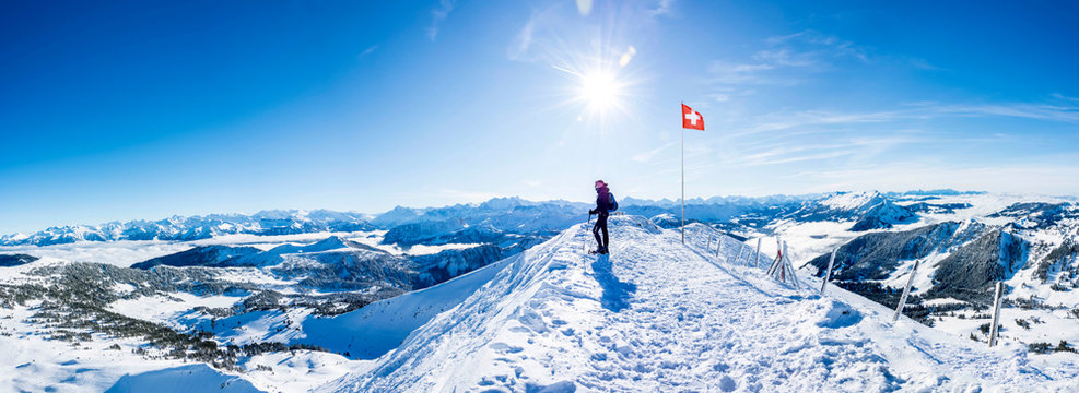 winter sports: snow shoe hiker a the summit of the snowy mountain in the swiss alps. panoramic switzerland mountain range