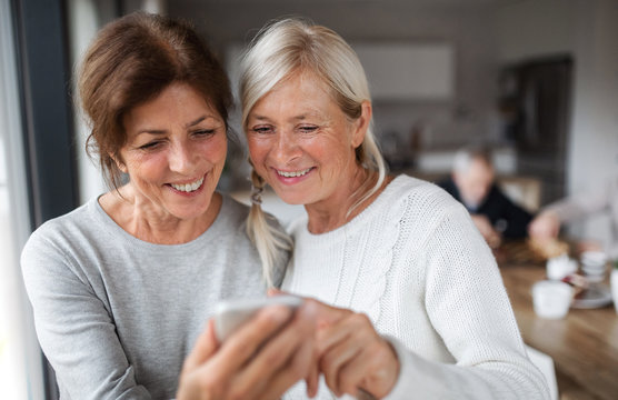 Group of senior friends at home, using smartphone.
