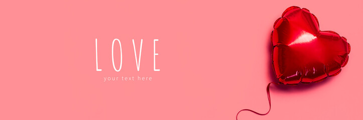 Love concept. Red balloon in the shape of heart on pink background top view flat lay copy space. Holiday Object, Birthday, Valentine's Day, Wedding. Party decoration. Greeting card