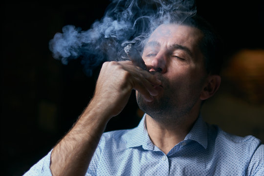 portrait of hansome man smoking cigar in a lounge bar