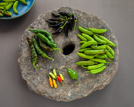 Variety of different chilies: serrano, habanero, tabasco, de cayene long slim, de cayene purple on stone with hole. Peppers in different stage of ripeness and pungency scale.
