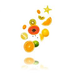 Fresh fruits flying in air. Papaya, orange, kiwi, lemon isolated on white background. Healthy fruity vegan tropical mix background. Colorful levitation, falling fly fruit creative concept