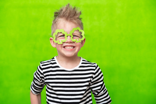 portrait little smiling caucasian boy in mask of leprechaun shamrock clover glasses for irish St. Patrick's Day on green studio background. Copyspace.