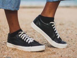 Modelo posando zapatillas negras con bordes blancos, cordones blancos, medias negras, sobre arena de playa Wall mural
