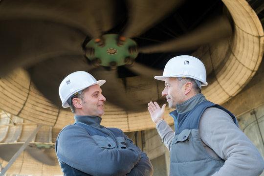 portrait of workers next to turbine