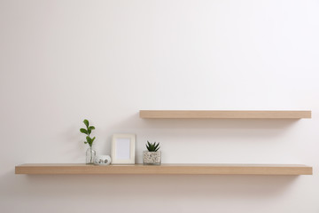 Wooden shelves with plants and photo frame on light wall