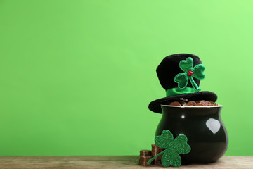Pot of gold coins, hat and clover on wooden table against green background, space for text. St. Patrick's Day celebration Wall mural