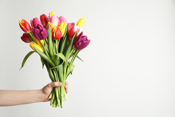 Woman holding beautiful spring tulips on white background, closeup. Space for text Fotobehang