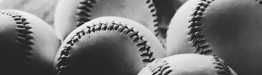 Close up of baseballs with seams, shows detail of balls in black and white banner.