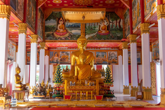 Wat Si Saket, a large golden Buddha statue and altar with offerings and wall murals, Vientiane, Laos,Vientiane