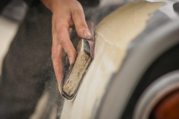 A hand of a man is seen sanding an old vintage car using a block of wood and brown sand grit paper. Manual dry sanding of a car in restoration, a process where putty is removed from bodywork. Wall mural