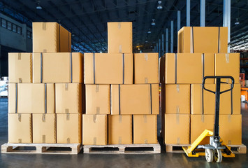 Obraz Stack of package boxes on wooden pallets and hand pallet truck in interior warehouse, Industrial warehouse delivery shipment goods, Cargo and logistics - fototapety do salonu