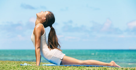 Yoga woman practicing yoga cobra pose at outdoors summer park. Beautiful girl stretching on yoga practice asana in yoga retreat. Happy healthy happiness. Horizontal background,