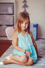 Cute adorable pretty dressed preschool girl playing a fairy princess at home. Child creativity imagination and fantasy dreams concept. Beautiful Caucasian kid in blue dress pretending a fairy or elf.