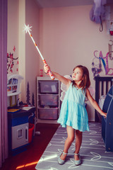 Cute adorable pretty dressed preschool girl playing fairy princess at home. Child creativity imagination and fantasy dreams concept. A beautiful kid in dress pretending to be fairy or elf.