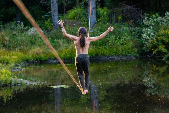 A male slack wire artist is seen practicing slacklining over a water pond in nature, balancing on rope anchored between two trees in woodland with copy space