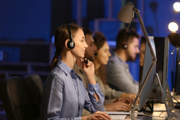 Technical support agents working in office at night