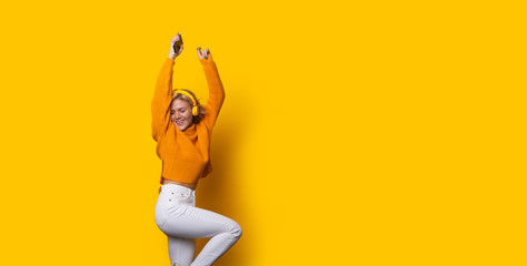 Stunning blonde caucasian girl dressed in an orange sweater and white jeans is dancing while posing on a yellow background and listening to music