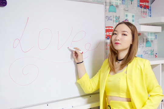 beautiful asian female student in classroom with whiteboard writing love
